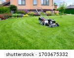 A Lawn Mower On A Lush Green...
