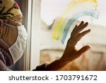 Small photo of An old grandmother in a protective mask looks out the window at self-isolation. Elderly woman at quarantine at home. Grandmother looks through the rainbow on the window pane into the street with a clo