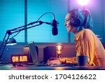 Small photo of Young radio host working in the studio, she is smiling and broadcasting announcements