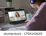 Small photo of Pc screen view over woman shoulder, two girls best friends chatting using virtual modern video conference application communicating from home enjoy distant talk. Teacher teach learner remotely concept