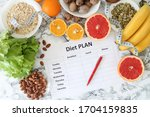 Small photo of Healthy eating, dieting, slimming and weigh loss concept - closeup of diet plan paper with fruit, nuts and centimeter.