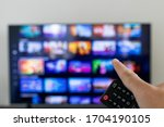 Small photo of Remote controller and tv blurred in background. Video streaming service catalogue in grid blurred on smart TV.