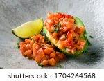 Small photo of Raw salmon tartare, trout tartar or red fish cubes salad with fresh avocado closeup. Macro shot of delicious raw tuna steak tartar or sashimi tapas on avocado