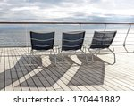 Empty deckchairs on deck of cruise ship - stock photo