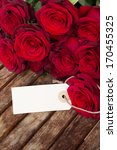 Stock photo dark red roses and tag on wooden table 170455325