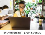 Small photo of European female gardener in glasses using laptop, scrolling through social networks, reads news, coffee/tea mug on table, home garden/greenhouse on background. Cozy workplace, remote work