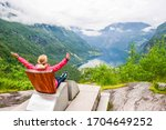 Female tourist sitting on the Queen Sony Chair at the Flydalsjuvet Viewpoint. The summer landscape of Geiranger small village which is located at the end of the Geirangerfjord. Norway.