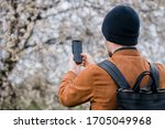 Small photo of Man taking a picture of apple blossoms tree. Trendy Hipster with a Beanie and ascetic backpack Behind shoulder view. Online influencer doing live streaming. Male hand taking photo of spring