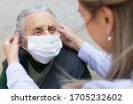 Nurse Putting On Surgical Mask...