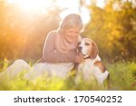 Stock photo senior woman hugs her beagle dog in countryside 170540252