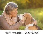 Stock photo senior woman hugs her beagle dog in countryside 170540258