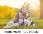 Stock photo senior woman hugs her beagle dog in countryside 170540882
