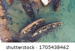 Small photo of The rusty remains of the old cargo ship on the shallow water, aerial top view. Footage. Skeleton of a destroyed seagoing ship near the shore.