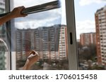 Small photo of tinted glass in the house. window dimming by dark film. tinting home window. tint film on the background of multi-storey buildings. window view through tinted glass