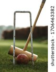 Small photo of Croquet mallet, ball and game on an English garden.