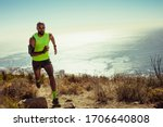Small photo of Full length of fitness man running over rocky trail on mountain. Fit young man running up a hill.