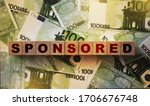 Small photo of SPONSORED word on wooden cubes put on many 100 Euro banknotes. Sponsor fundrising funding financing business startup concept.