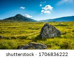 Foreground rock amidst backlit green grass and rolling hills - stock photo