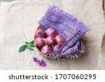 beautiful big purple red bulb onions are arranged elegantly in a basket near colorful jute bag