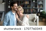 Small photo of Horizontal wide image inside of cozy living room at home standing hugging middle-aged mother and grown up adult millennial son. Family bonds and values, love care and relatives closest people concept