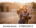 A young cowgirl woman stroking...