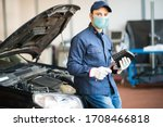 Masked Car Mechanic Holding A...