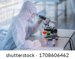 Small photo of Male scientist testing experiment in a science lab where he holding scientific test tube full of chemical substance. The researcher is analyzing medicine related innovation. Microbiology concept.