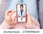 Small photo of Asian chinese doctor or therapist help releave stress from coronavirus crisis video conference call online live talk remotely with woman sit on sofa couch at home using smartphone doctor consultation.