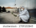 Small photo of Depressed crying doctor with mask having mental breakdown.Fear,anxiety,panic attack due to coronavirus outbreak.Psychological effects of COVID-19.PTSD.Mental health,coping with death