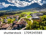 Small photo of Aerial view of improbable green meadows of Italian Alps, Comano Terme, huge clouds over a valley, roof tops of houses, Dolomites on background, sunshines through clouds