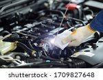 Small photo of car mechanic checking oil level in a mechanical workshop Cropped image of two handsome mechanics in uniform are working in auto service. Car repair and maintenance. Checking the oil level.
