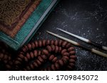 Muslim Holy Book of Quran With Rosary or tasbih and porcupine quills isolated on Black Background. Desaturated low key photography.