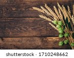 Small photo of Beer brewing ingredients Hop and wheat ears on wooden cracked old table. Beer brewery concept. Hop cones and wheat closeup. Sack of hops and sheaf of wheat on vintage background.