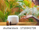 Small photo of Woman Enjoying Aroma Therapy Steam Scent from Home Essential Oil Diffuser or Air Humidifier. Ultrasonic technology, increasing air humidity indoors for more comfortable living conditions
