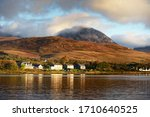 Panoramic view of the valley near the Paps of Jura under the colorful stormy sunset sky. Traditional country houses close-up. Dramatic cloudscape. Jura island, Inner Hebrides, Scotland, UK
