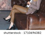 Woman Sitting On Leather Sofa...