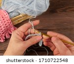 Small photo of Female hands knit crocheted from a wool thread of light blue colour next to a wicker box, in which contain a skein of yarn and ready-made knitwear on a wooden table.