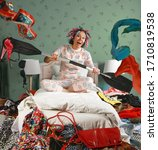 Small photo of Middle aged woman in pajamas and curlers is sitting on a bed paddling as if in a boat through a pile of scattered clothing in complete disarray. The theme of excessive consumption of things