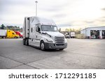 Small photo of Big rig bonnet diesel industrial semi truck with reefer semi trailer turning around on the wide truck stop parking lot with another semi trucks standing in row and truck maintenance boxes