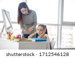 Small photo of Reluctance to learn. Young long-haired mother standing talking with a school-aged daughter sitting at the table in a sad mood.