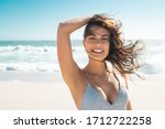 Small photo of Young smiling woman in bikini at tropical beach looking at camera. Portrait of beautiful latin girl in swimwear with ocean in background. Happy tanned hispanic woman relaxing at sea and copy space.