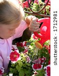 Little girl watering flowers - stock photo