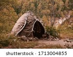 Small photo of Hut of ancient people. Prehistoric dwelling place, primitive architecture. Wigwam made of animal skins surrounded with mammoth tusks. The cabin of an ancient man. Leathers shelter of primitive man