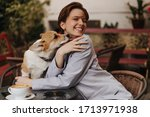 Optimistic woman in grey suit smiling and playing with dog in cafe. Pretty short-haired lady in stylish jacket poses with corgi outside - stock photo