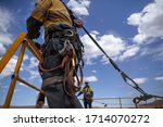 Small photo of Safe workplace rigger wearing working at heights harness clipping an inertia reel shock absorbing fall arrest device hook on the rope sling anchor point while working from 2 metre exposure open edges