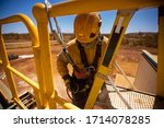 Small photo of Safety workplace defocused construction worker wearing yellow safety helmet, fall arrest PPE harness attached an inertia reel shock absorber device on harness safety loop while standing on ladder