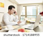 Small photo of young asian man design professional working from home sitting at kitchen talking on mobile phone (artwork in background digitally altered)