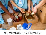 Small photo of Homeless care. Charity team of volunteers putting food and drinks into paper box. Volunteers Collecting Food Donations In Warehouse. Volunteers with donation box with foodstuffs on wooden background