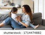 Smiling Mommy Sitting On Sofa...