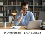 Small photo of Smiling businessman wearing glasses talking on phone, sitting at desk with laptop, friendly manager consulting customer by phone, happy man chatting with friends distracted from work